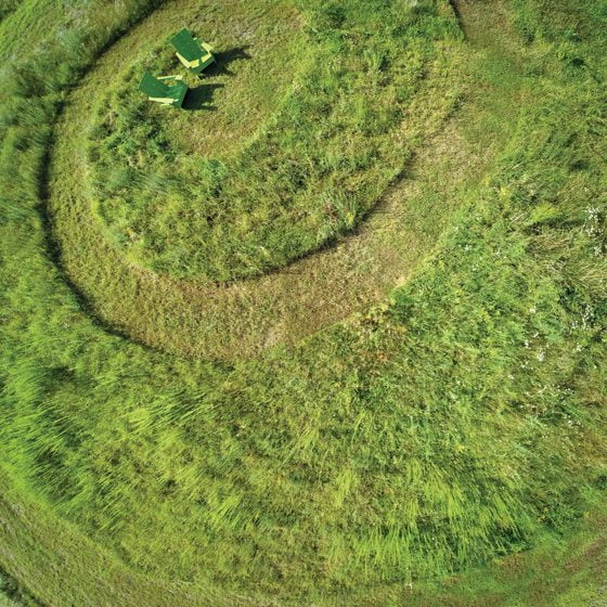 A nature-inspired spiral is cut into an open meadow.
