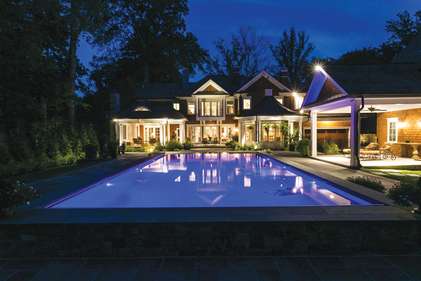 Sandy Spring Builders crafted a sprawling, traditional home with a patio that spills out to the pool and adjoining pool house.