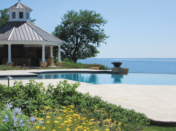 Connoley designed a 15,000-square-foot entertaining area to transition seamlessly from the inside out, connecting the residence with its waterfront environment. Working with contractor Solidago Landscapes, LLC, she raised the grade, adding wide steps and travertine pavers, natural drift plantings and a bay-friendly pool color. © Jennifer Connoley