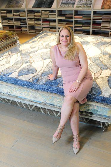 Stephanie Gamble luxuriates on fine carpets in the Stark showroom. © Michael Ventura