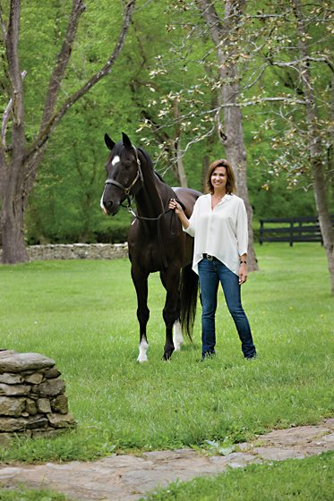 Designer Natascha Folens stands in the front yard with her horse, Venture.