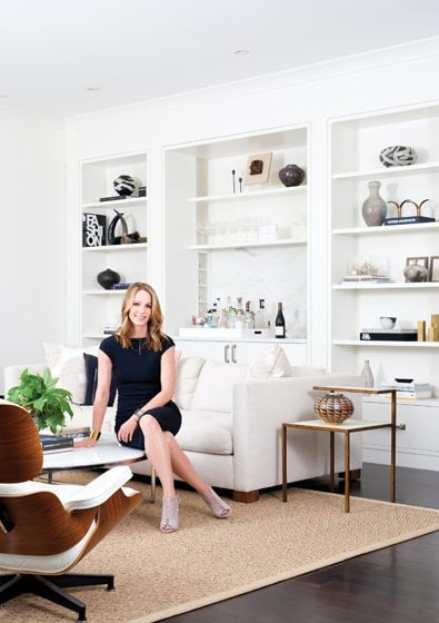 Sandra Meyer sits in the family room, where she designed a minimalist wall of shelves containing a built-in bar.