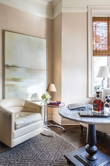 A vintage leather chair and a calming abstract canvas imbued the sitting room with a cozy feel.