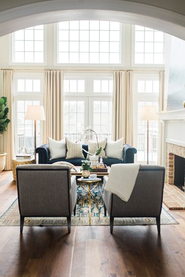 In the living room, seating centers around an antique rug.