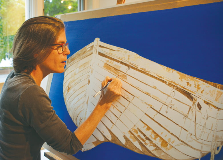 The artist, who splits her time between homes and studios in DC and Maine, paints a wooden boat.
