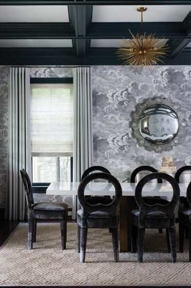 The dining room features Cole and Son wallpaper and velvet-covered chairs designed by Meyer.