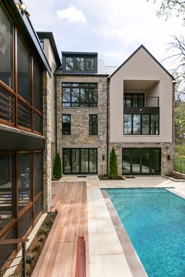 Sandy Spring Builders crafted a contemporary home with a stone exterior and an inviting lap pool.