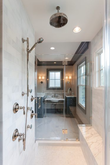 The gray QuakerMaid cabinets and trim echo the veining in the Calacatta Chablis marble flooring and shower tile.