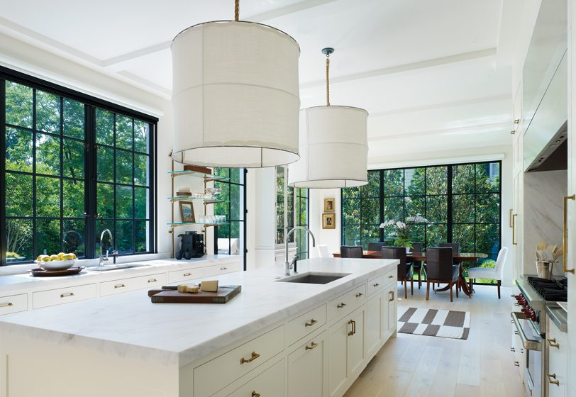 In the airy, white kitchen, steel-framed windows showcase views of the garden.