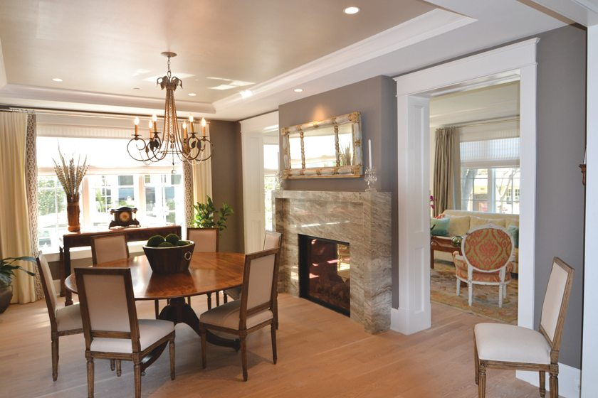 A tray ceiling and stone fireplace embellish the dining room in a home by Studio Z Design Concepts, LLC.