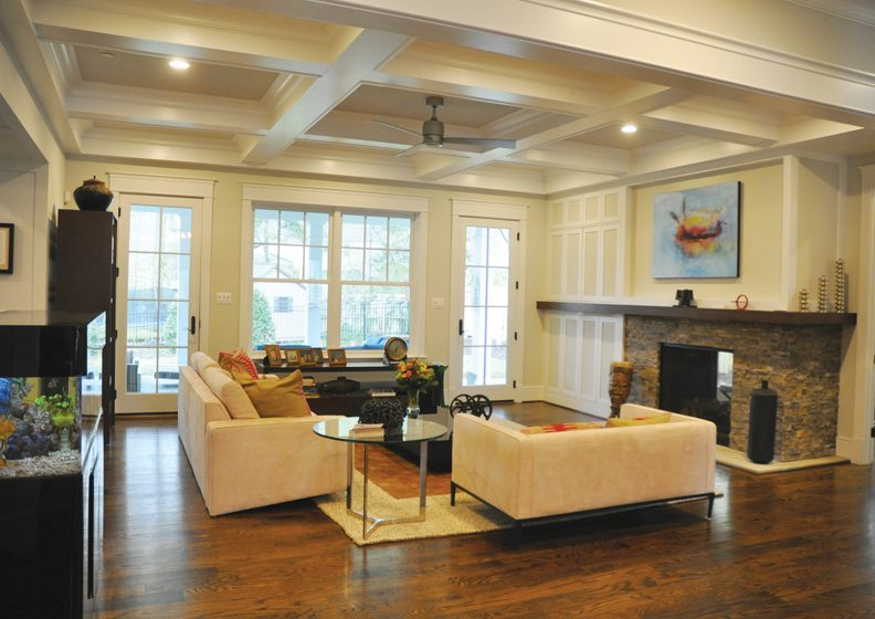 A transitional residence by Carter, Inc., houses a family room with a coffered ceiling and stone hearth.