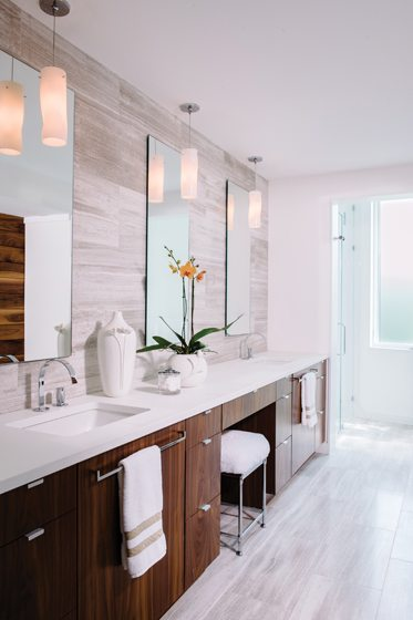 A double vanity with Pure White Thassos marble countertops and richly grained walnut cabinetry lines one wall.