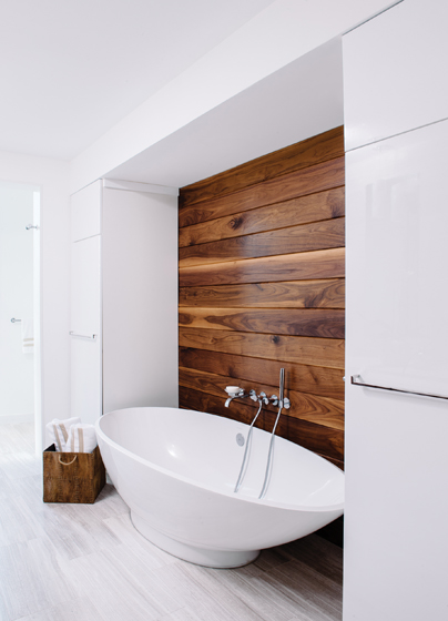A contrasting, custom tongue-in-groove inset wall in walnut frames the tub.