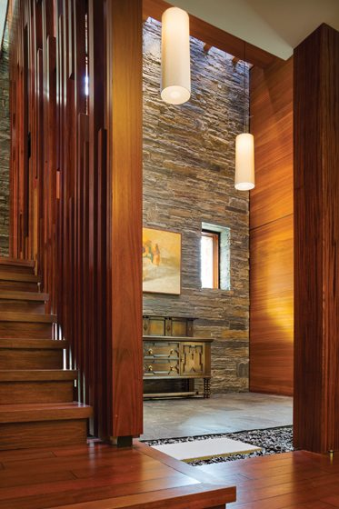 The foyer combines a stone wall, a bluestone floor and a stair wall of mahogany panels.