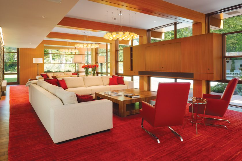 In the family room, one seating arrangement faces a cabinet concealing a TV.
