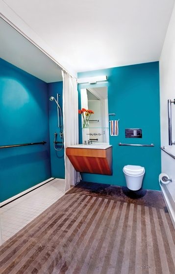 The brightly hued baths boast cantilevered fir vanities and acid-etched, non-slip concrete floors.