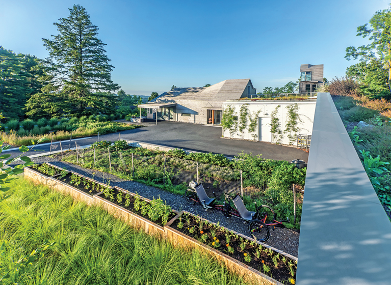 A view of the house from atop the concrete wall reveals an extensive vegetable garden.