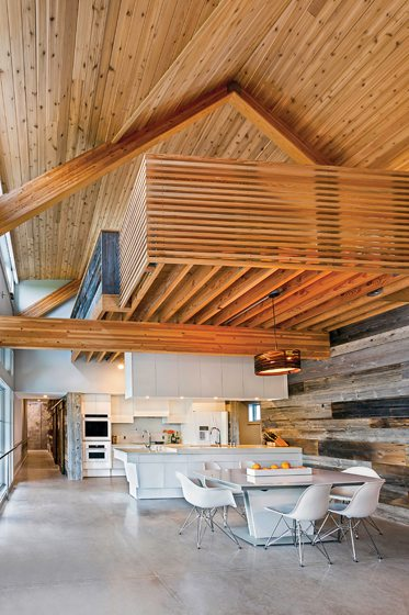 The kitchen/dining area features a wall of reclaimed barn wood with a cedar-enclosed loft above.