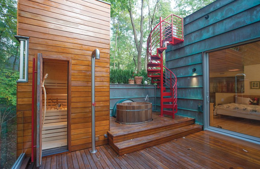 The soaking tub is flanked by a sauna on one side and stairs to the upper deck on the other.