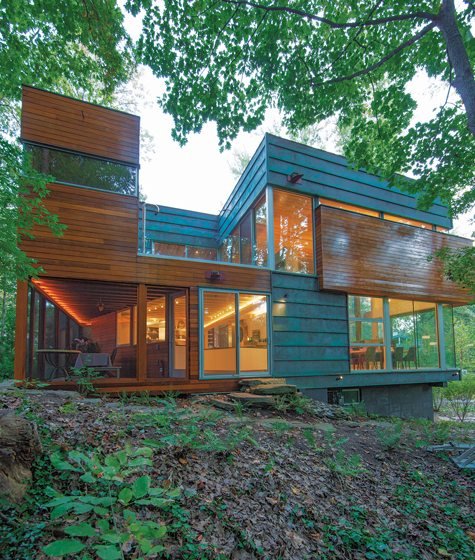 Panels of oxidized copper, cedar and glass break up the mass of the three-level house.