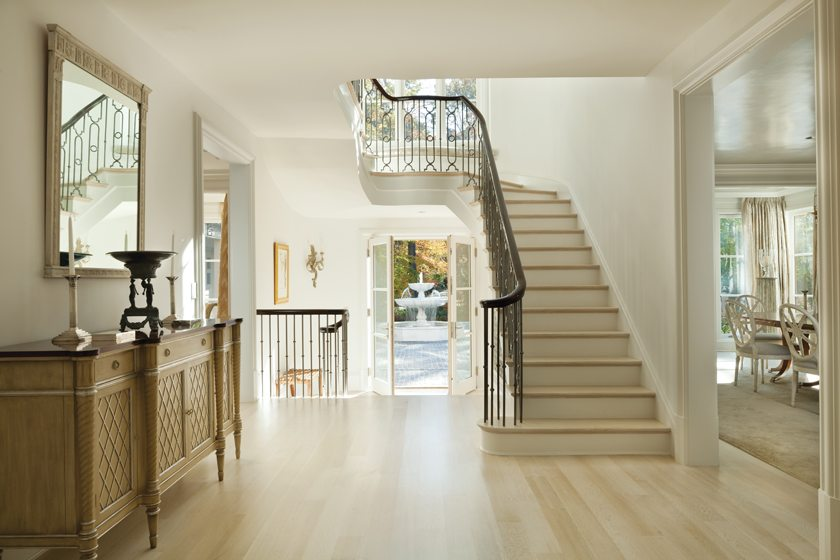 The home's restrained style begins in the foyer, with its dramatic staircase.