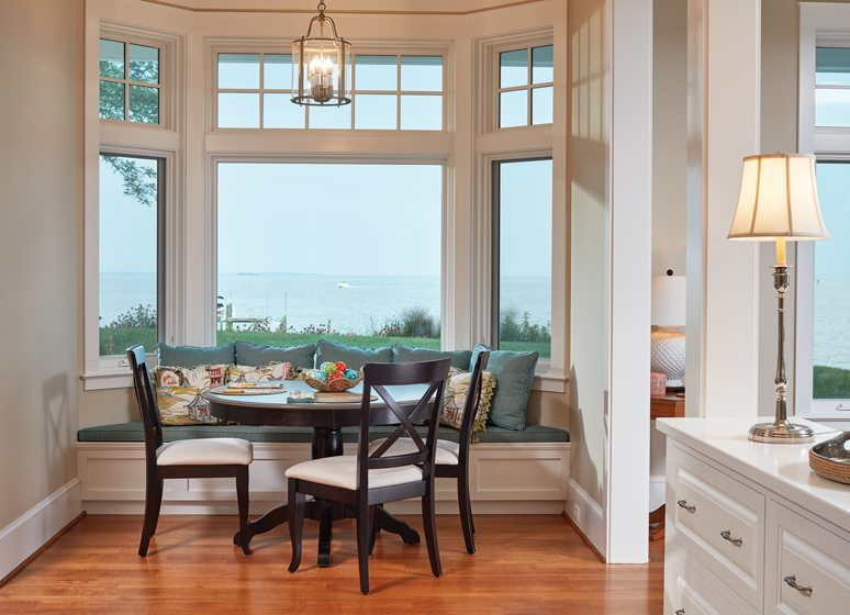In the breakfast nook, a table and built-in banquette serve up water views.