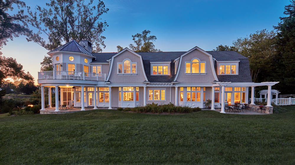 New England Shingle-style architectural elements include gambrel rooflines with flared eaves and a turret.