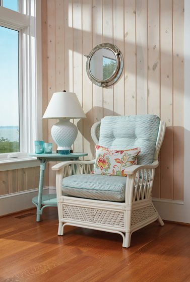 The sunroom is clad in crisp, white-washed pine boards.