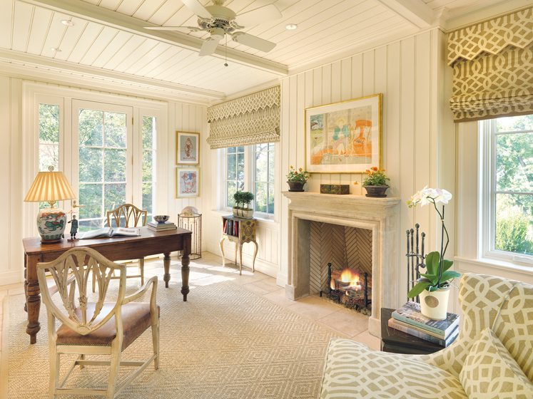 Painted paneling, a French limestone fireplace and an antique desk enliven the wife's home office.