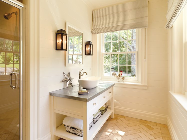 The custom vanity with a zinc top conveys a more casual vibe in a new bath.