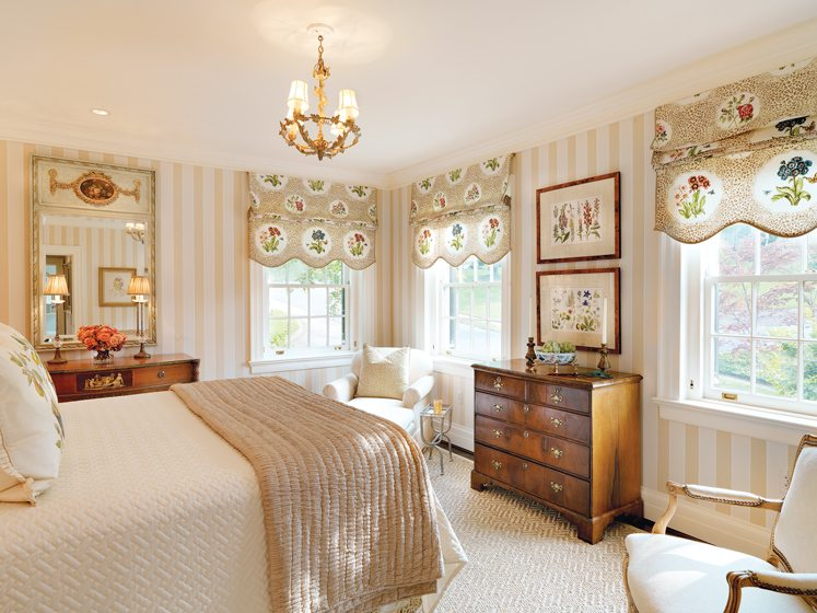 A guest room is embellished with window treatment fabric by Osborne & Little.