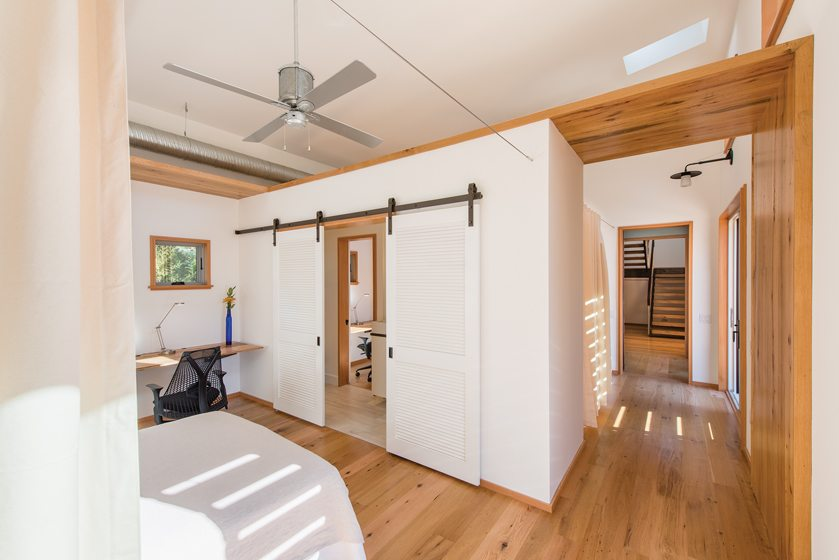 The bedrooms are separated by a slab of Douglas fir above the passageway.