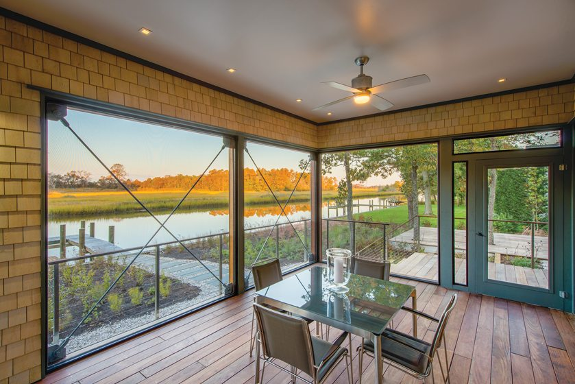 The screened porch, visible through sliding-glass doors, overlooks the canal.