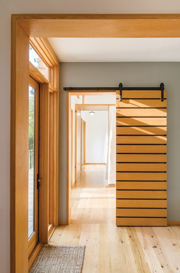 """At the front entry, a barn door opens to """"the bunkhouse"""" wing."""