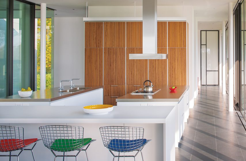 In the kitchen, Bertoia bar stools add color; the wood cabinets are from Bulthaup.