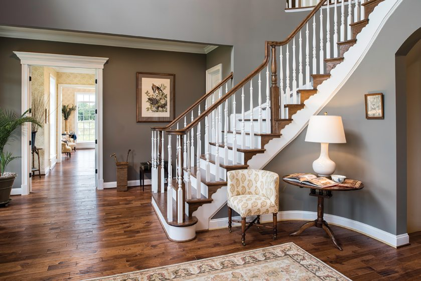 A two-story foyer boasts a curved oak staircase.