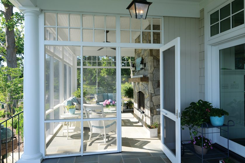The screened porch boasts a wood-burning fireplace and wicker furniture from Great Gatherings.