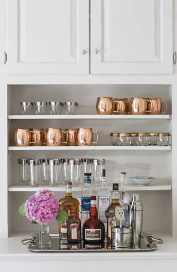 A shelf unit in the wife's study houses a bar.