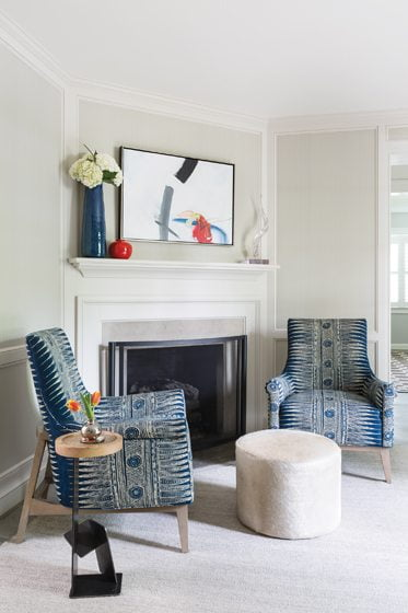 Batik-like indigo fabric from Lee Jofa covers armchairs by the fireplace.