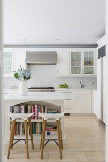 The kitchen cabinetry was painted white and a backsplash of Calacatta Gold tiles was added.