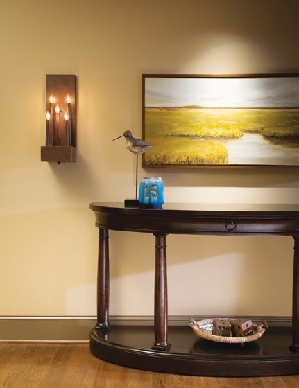 On the lower level, a hallway with a Bernhardt console and Solaria sconces leads into the media room.