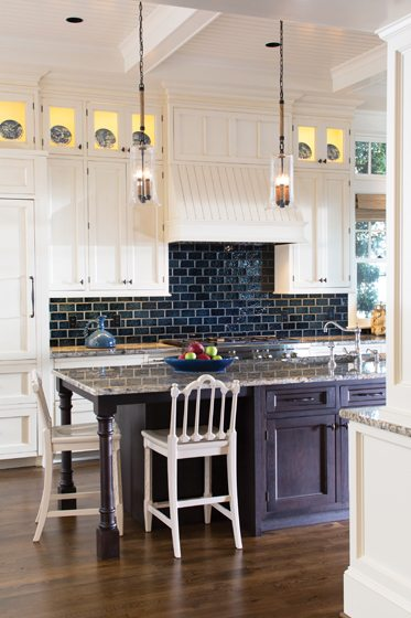 A granite-topped island contrasts with the lighter peripheral cabinetry.