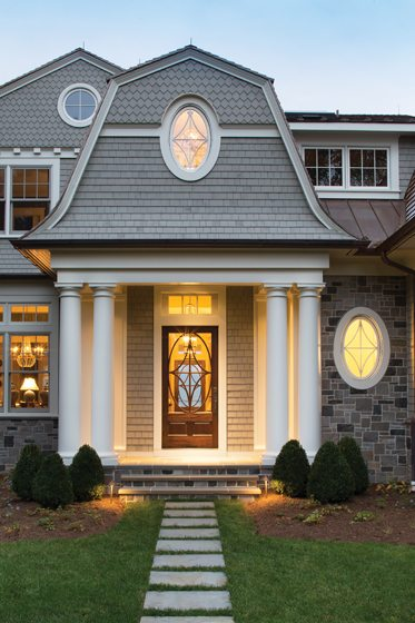 The main entry welcomes guests into the home clad in stone and shingles.