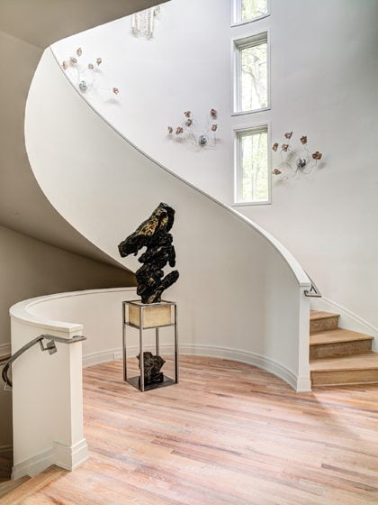 The foyer's dramatic, curved stairway was inspired by the one in New York's Guggenheim Museum.