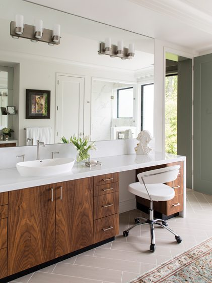 Carrara marble counters top custom walnut cabinetry in the master bath.