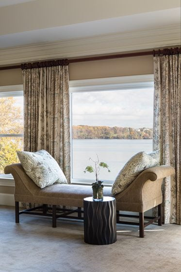 Window panels in a Lee Jofa print frame a graceful bench by Hickory Chair in the master suite.