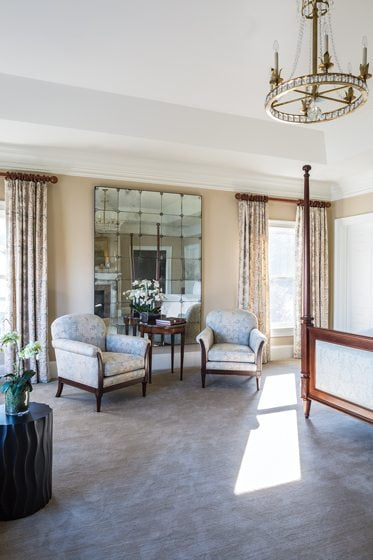 In the master bedroom, club chairs flank an antique French marquetry table.