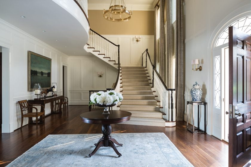 In the stately foyer, a pair of antique Regency chairs flanks a David Iatesta console.