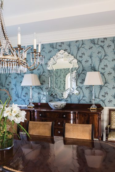 Jim Thompson wallpaper creates an elegant backdrop for dinners around the Kittinger table; the chairs are from Hickory Chair.