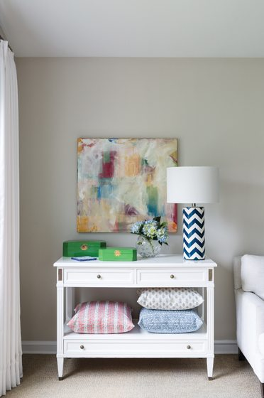 The pastel hues of throw pillows beautifully complement a piece of abstract art, also created by Meyer.